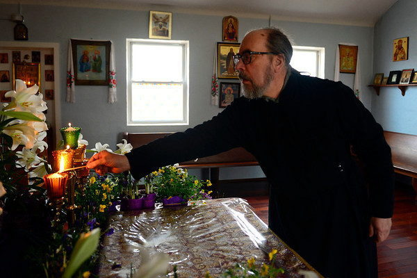 BEN MIKESELL | THE GOSHEN NEWS<br /> The Rev. Alexander Mintairov of South Bend lights candles prior to the Good Friday service Friday at Holy Virgin Protection Orthodox Church in Goshen. The Orthodox Church celebrated Easter Sunday.