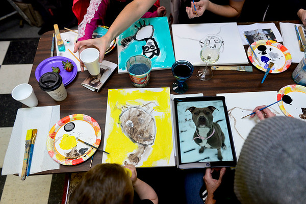 BEN MIKESELL   THE GOSHEN NEWS<br /> Andrea Sandusky and her son Landon, 4, of Goshen paint pictures of their pit bull Dahlia during Pet Portrait Day Thursday at Home Again Consignment.