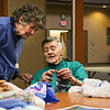 LEANDRA BEABOUT | THE GOSHEN NEWS<br /> Laverne Nafziger, right, helps Gretta Peterson with a difficult stitch during Greencroft Goshen's Monday afternoon knitting group. The informal group meets at the Community Center from 1-3 p.m. weekly and is free of charge.