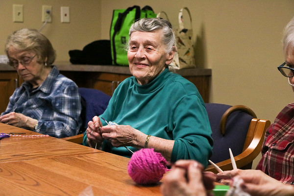 LEANDRA BEABOUT | THE GOSHEN NEWS<br /> Laverne Nafziger, center, is the unofficial leader of Greencroft Goshen's knitting group. She helped several women Monday as they learned new patterns or tried new methods with their yarn.