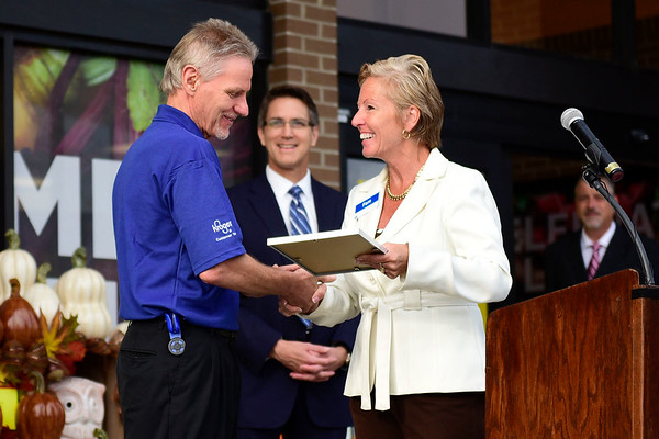 BEN MIKESELL | THE GOSHEN NEWS<br /> Jeff Cors, produce department leader at Kroger, is presented with an award for working at Kroger for 50 years during the grand reopening of the Kroger store Wednesday morning in Goshen.