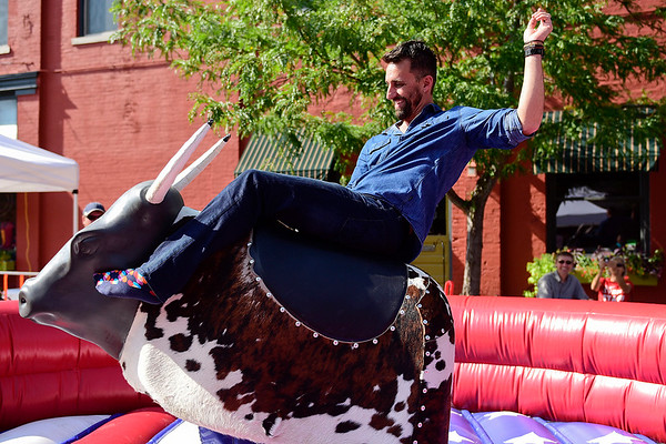 BEN MIKESELL | THE GOSHEN NEWS<br /> Mayor Jeremy Stutsman rides the mechanical bull during Friday's Cornfest in downtown Goshen.