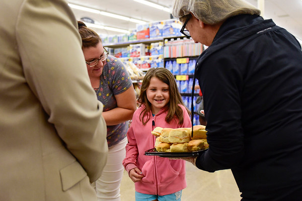 BEN MIKESELL | THE GOSHEN NEWS<br /> Gabriella Alvarez, 8, with her mother Heather, takes a free sandwich sample while inside the newly renovated Kroger store during its grand reopening Wednesday morning in Goshen.