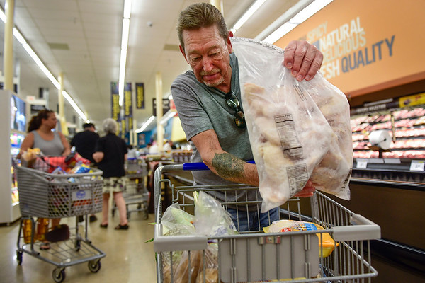 BEN MIKESELL | THE GOSHEN NEWS<br /> Goshen resident Jim Balser puts chicken wings into his cart while grocery shopping during the grand reopening of Kroger Wednesday morning in Goshen.
