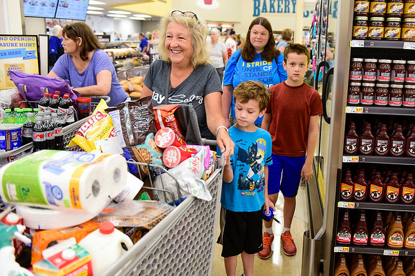 BEN MIKESELL | THE GOSHEN NEWS<br /> Dana Mehl, of Goshen, goes grocery shopping with her grandkids Kevin and Chris, and their mother LeAnn, of Elkhart, during the grand reopening of the Kroger store Wednesday morning in Goshen.
