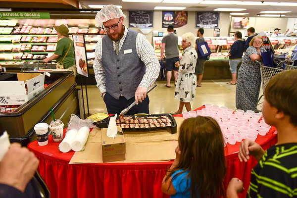 BEN MIKESELL | THE GOSHEN NEWS<br /> Jeremy Hardwick with Empire, a food vendor for Kroger, whips up free samples of bacon for customers inside the newly renovated Kroger store Wednesday morning.