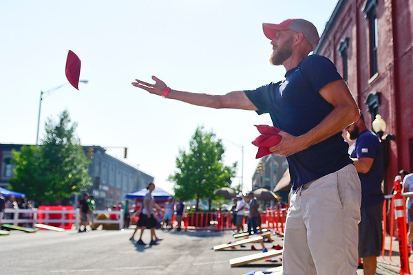 BEN MIKESELL | THE GOSHEN NEWS<br /> Nick Battles, of Goshen, gets some practice tosses in before the cornhole tournament Friday, as part of First Friday's Cornfest in downtown Goshen.