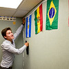 BEN MIKESELL | THE GOSHEN NEWS<br /> Alejandro Rodriguez hangs flags from Latino countries around his classroom Friday at West Goshen Elementary School. He will be teaching EL classes at West Goshen this year as part of Goshen College's EL program for full-time teachers.