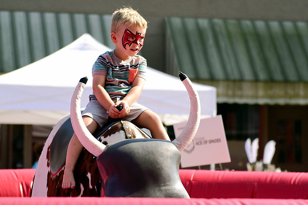 BEN MIKESELL | THE GOSHEN NEWS<br /> Ford Tarman, 2, of Goshen rides the mechanical bull during Friday's Cornfest in downtown Goshen.