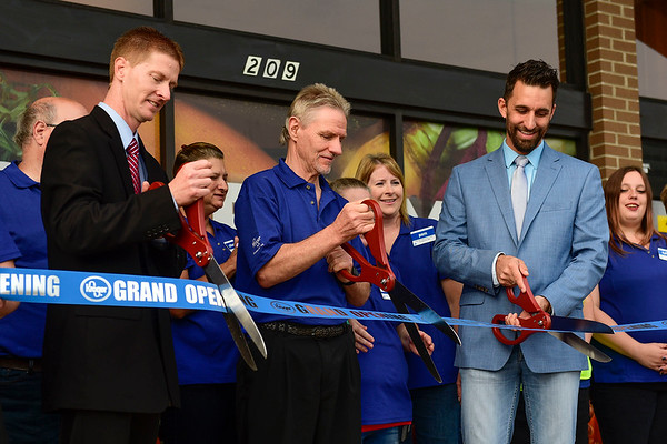 BEN MIKESELL | THE GOSHEN NEWS<br /> Store manager Charles Neuwirth, left, produce leader Jeff Cors, and mayor Jeremy Stutsman cut the ribbon Wednesday morning, marking the grand reopening of the Kroger store in Goshen.