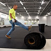 BEN MIKESELL | THE GOSHEN NEWS<br /> Paul Roeder, with Connor Sports in Chicago, rolls out new flooring for the new weight room in the Athletic Center Tuesday morning at NorthWood High School in Nappanee.