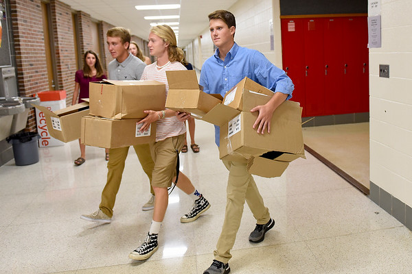 BEN MIKESELL | THE GOSHEN NEWS<br /> Student council members from left, junior Cooper Davis, junior Skyler Duerksen and freshman Cole Davis carry cardboard boxes across the school while helping teachers set up their classrooms before the first day of school Tuesday morning at NorthWood High School.