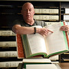 BEN MIKESELL | THE GOSHEN NEWS<br /> Chief deputy clerk Christopher Anderson pulls out a historical docket in one of the vault rooms during a tour Thursday morning at the Elkhart County Courthouse.