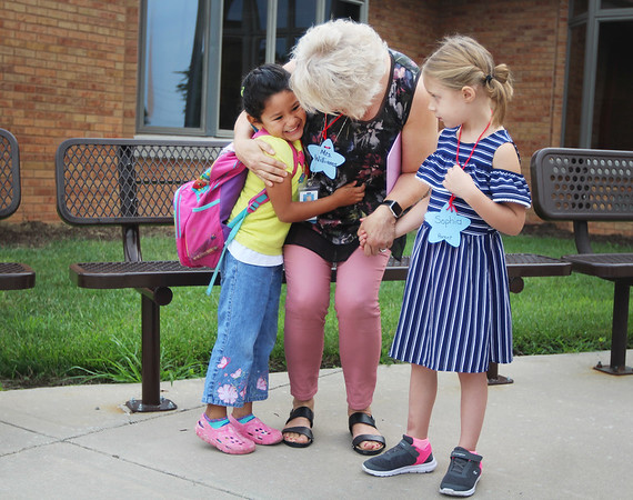JULIE CROTHERS BEER | THE GOSHEN NEWS<br /> Kindergartener Betsaida Martinez hugs her new teacher Melanie Williams as her classmate Sophia Griffith looks on during the first day of school Wednesday at Woodview Elementary School in Nappanee.