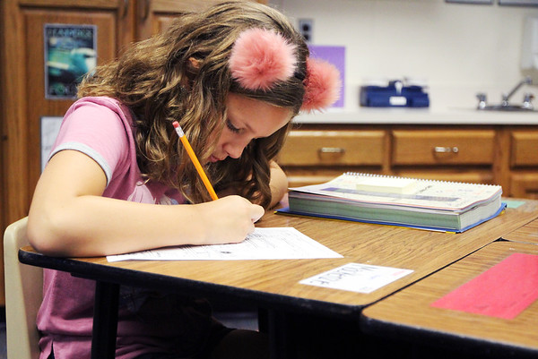JULIE CROTHERS BEER | THE GOSHEN NEWS<br /> Donning a fuzzy headband, fourth-grader MacKenzie Miller works on a worksheet Wednesday during her first day of school at Woodview Elementary School in Nappanee.