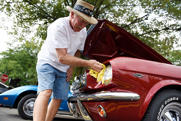 BEN MIKESELL | THE GOSHEN NEWS<br /> Dale Schultz, of Three Rivers, Michigan, wipes down his 1965 Ford Mustang during Millersburg Street Fest Friday night. The festival continues today in downtown Millersburg.