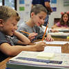 JULIE CROTHERS BEER | THE GOSHEN NEWS<br /> Classmates Brett Guard and Kian Hornish work on a worksheet Wednesday during their first day of fourth grade at Woodview Elementary School in Nappanee.