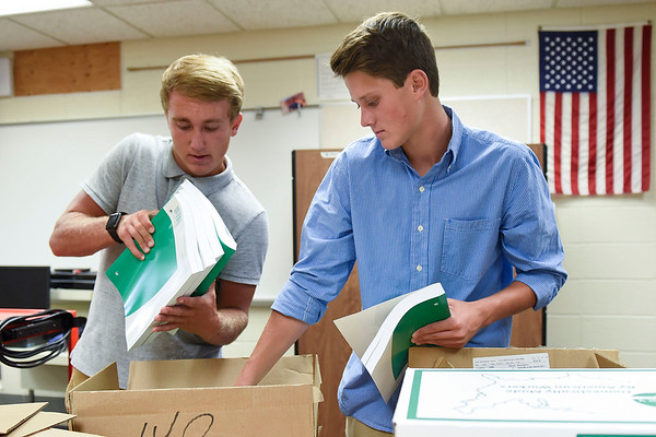 BEN MIKESELL | THE GOSHEN NEWS<br /> Siblings Cooper Davis, junior, left, and Cole Davis, freshman, right, help unpack workbooks in Joel Mishler's business classroom Tuesday morning at NorthWood High School. The brothers were assisting teachers across the school along with other members of student council.
