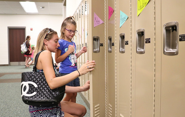 "LEANDRA BEABOUT | THE GOSHEN NEWS<br /> Marissa Rowe helps her daughter Milee Rowe, 5, open a locker on ""Back to School"" night at Syracuse Elementary School."