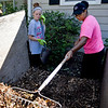 BEN MIKESELL | THE GOSHEN NEWS<br /> Goshen College soccer players junior Alexis Johnson, left, and Arenna Holifield, right, scoop out mulch while landscaping Wednesday morning along College Avenue near campus.