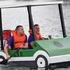 BEN MIKESELL | THE GOSHEN NEWS<br /> Chris Landis, of Granger, left, and Yuriy Panchelyuga, of Goshen round turn four in their golf cart-shaped boat during United Way's Great Cardboard Boat Race Friday afternoon in Elkhart.