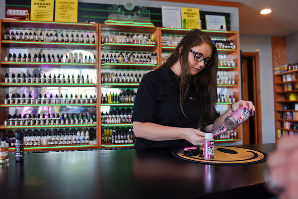 BEN MIKESELL | THE GOSHEN NEWS<br /> Cravin Vapes general manager Kayley Patton helps a customer with a bottle of e-liquid Thursday morning at the store on Pike Street in Goshen.