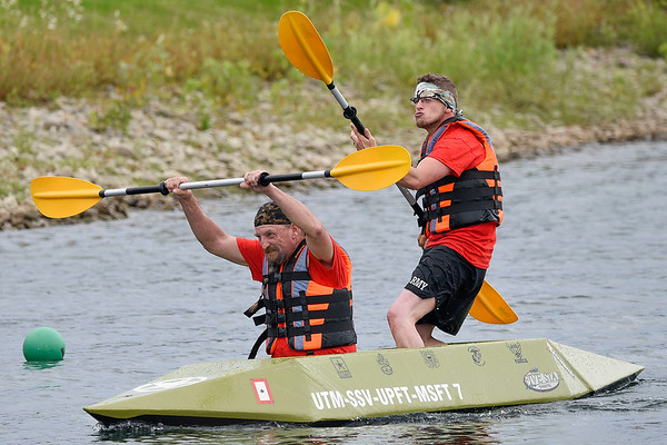 BEN MIKESELL | THE GOSHEN NEWS<br /> Danny Arch, of Bristol, left, celebrates with partner Mark Johnson, of Bristol, who plays the guitar with his oar as they coast across the finish line the second heat of United Way's Great Cardboard Boat Race Friday afternoon in Elkhart.