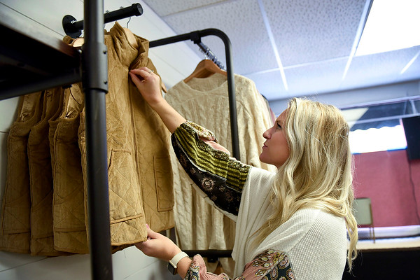 BEN MIKESELL | THE GOSHEN NEWS<br /> Elise Wright hangs up clothes inside Elysian Co., her new store on West Washington Street in downtown Goshen. Wright is co-owning the store with her sister Rochelle Stech, of Bristol.
