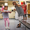 LEANDRA BEABOUT | THE GOSHEN NEWS<br /> Kindergarten student Fernanda Liera, 5, walks to her seat in the cafeteria on her first day of school at West Noble Primary School. Teacher Donna Risser helps point her in the right direction.