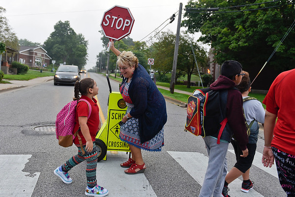 BEN MIKESELL | THE GOSHEN NEWS<br /> Tracy Noe, executive director of curriculum at Goshen Community Schools, greets kindergarten student Sheila Garrett as she helps students cross Middlebury Road for the first day of school Wednesday at Chamberlain Elementary School.