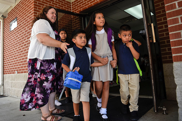 BEN MIKESELL | THE GOSHEN NEWS<br /> First grade teacher Stephanie Kronk, left, guides students to their vehicles to end the first day of school Wednesday afternoon at St. John Catholic Elementary School.
