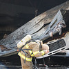 AIMEE AMBROSE | THE GOSHEN NEWS<br /> <br /> A firefighter removes his helmet and head gear after helping bring a fire under control at Marway Welding, 27097 C.R. 50, near Nappanee Monday morning.