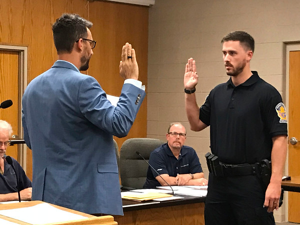 JOHN KLINE | THE GOSHEN NEWS<br /> Goshen Mayor Jeremy Stutsman, left, delivers the oath of office to Justin L. Scott following his promotion from the rank of probationary patrol officer to the rank of patrol officer with the Goshen Police Department during Monday's Board of Public Works and Safety meeting.