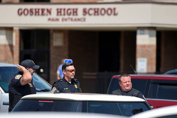 BEN MIKESELL | THE GOSHEN NEWS<br /> Goshen police officers, from left, David Miller, Stu Smith and Mike Johnson stay on the scene where a B.B. gun was found Thursday afternoon in the parking lot of Goshen High School.