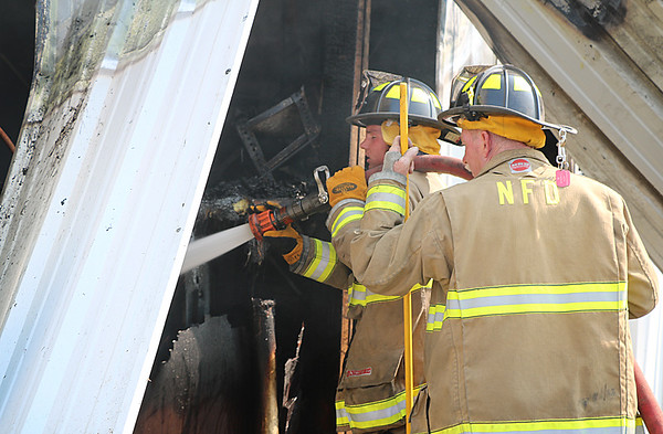 AIMEE AMBROSE | THE GOSHEN NEWS  Nappanee firefighters extinguish a hot spot at the scene of a fire that destroyed the Marway Welding shop, 27097 C.R. 50, Monday morning.