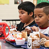 LEANDRA BEABOUT | THE GOSHEN NEWS<br /> Kindergartener Victor Silva, right, gets his hamburger ready during lunch on the first day of school at West Noble Primary School. Behind him is classmate Noe Pedroza.