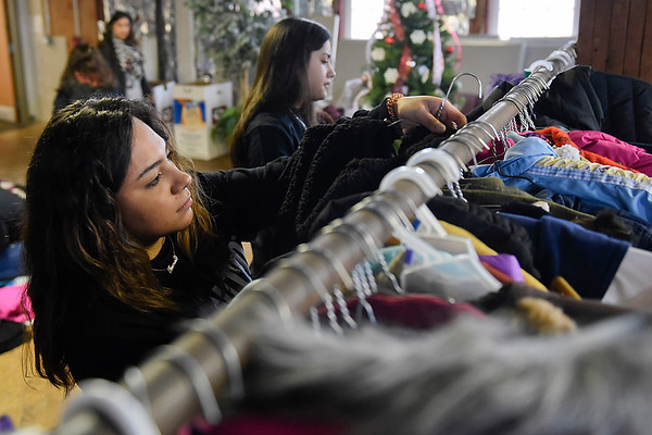 BEN MIKESELL | THE GOSHEN NEWS<br /> Goshen High School junior Ale Carmona places a coat on a rack while sorting for the annual United Way coat drive Wednesday afternoon at the Goshen Community Schools Administration Building.