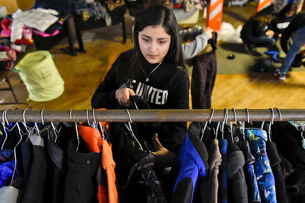 BEN MIKESELL   THE GOSHEN NEWS<br /> Goshen High School sophomore Lyzbet Rodriguez places a coat on a rack while sorting for the annual United Way coat drive Wednesday afternoon at the Goshen Community Schools Administration Building.