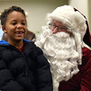 BEN MIKESELL | THE GOSHEN NEWS<br /> Bob Clayton, New Paris, dressed as Santa, listens to Julian Goeglein, 7, of New Paris, as he lists what he wants for Christmas Saturday morning at Interra Credit Union in New Paris. Clayton works with the New Paris Lions Club, who sponsored the event Saturday.