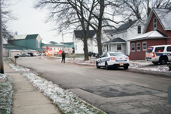 Roger Schneider | The Goshen News<br /> <br /> A Goshen police officer stands in front of a house at 407 Center St. (the red one), while other officers enter the house from the rear. The officers took a man into custody after a woman was injured in the parking lot outside the Boys & Girls Club on Crescent Street. The club can be seen in the background.