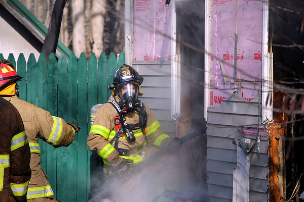 AIMEE AMBROSE | THE GOSHEN NEWS <br /> A firefighter works bring under control a fire that heavily damaged a house owned by John and Sharon Wood, 71247 Ind. 15, near New Paris Friday afternoon. Firefighters from New Paris and four other departments had responded to the scene.