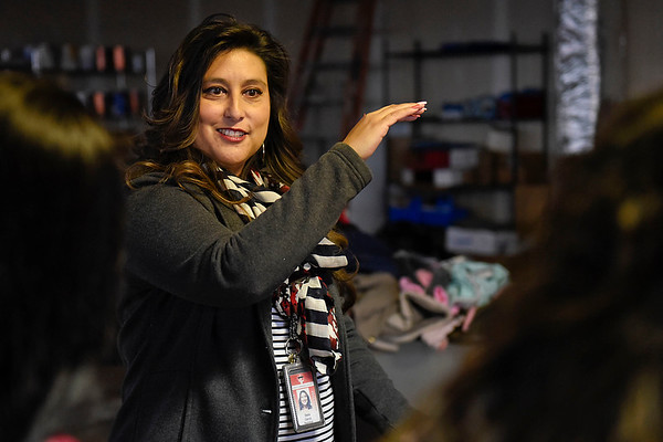 BEN MIKESELL | THE GOSHEN NEWS<br /> Central registrar Stella Garcia explains how to sort coats gathered for United Way's coat drive Wednesday at the Goshen Community Schools Administration Building.