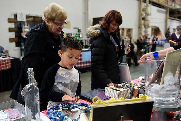 BEN MIKESELL | THE GOSHEN NEWS<br /> Eiljah Devlin, 5, Goshen, helps his mother Dana and grandmother Diana Francis shop at the Undercover Popular booth, run by Elizabeth O'Leary, at the Handmade Holiday Show Saturday morning at the Old Bag Factory. There were 68 vendors in this year's seventh annual holiday show, Pop Up Handicrafts owner Amanda Gobble said.