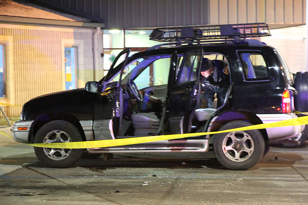 Roger Schneider   The Goshen News<br /> A Goshen police officer examines the interior of a car outside the Boys & Girls Club Wednesday night. A club official said a domestic disput led to a woman being attacked in her car and a man being taken into custody.