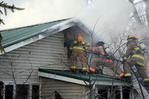 AIMEE AMBROSE | THE GOSHEN NEWS <br /> A New Paris firefighter, braced and aided by a Benton Township firefighter and another New Paris firefighter, spays water into the attic of a house owned by John and Sharon Wood, 71247 Ind. 15, to extinguish a fire Friday afternoon.