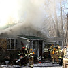 AIMEE AMBROSE | THE GOSHEN NEWS <br /> Firefighters work to bring a house fire under control. The home, owned by John and Sharon Wood, 71247 Ind. 15, near New Paris was heavily damaged by the fire Friday aftenroon.