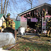 AIMEE AMBROSE | THE GOSHEN NEWS <br /> Firefighters check for and extinguish hot spots in an attic area after a fire heavily damaged the home of John and Sharon Wood, 71247 Ind. 15, near New Paris Friday afternoon.