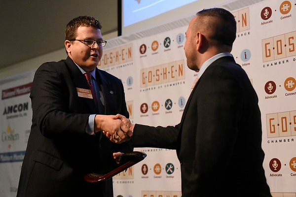 BEN MIKESELL | THE GOSHEN NEWS<br /> Goshen Chamber of Commerce President Nick Kieffer congratulates Lyle Miller, owner of Dutch Maid Bakery, as he is awarded the Maple Leaf Award for Small Business during the annual luncheon Thursday at Maple City Chapel.