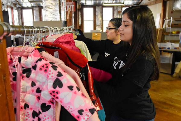 BEN MIKESELL | THE GOSHEN NEWS<br /> Goshen High School sophomore Lyzbet Rodriguez places a coat on a rack while sorting for the annual United Way coat drive Wednesday afternoon at the Goshen Community Schools Administration Building.