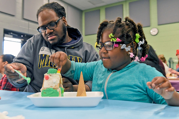 BEN MIKESELL | THE GOSHEN NEWS<br /> Kindergarten student Kendalynn Roberson, right, decorates a gingerbread house with the help of her father James Tuesday afternoon at Concord South Side Elementary School.